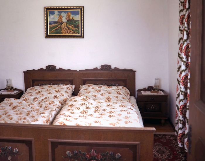 Großes Doppelbett mit traditioneller Bauernmalerei im zweiten Schlafzimmer der Ferienwohnung Gutenbrunner
