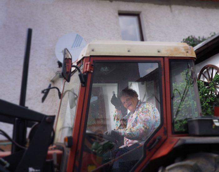 Bäuerin Maria im Traktor im Innenhof